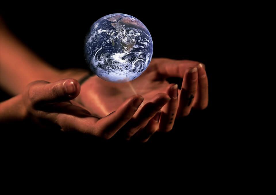 На фото изображена планета Земля в руках.