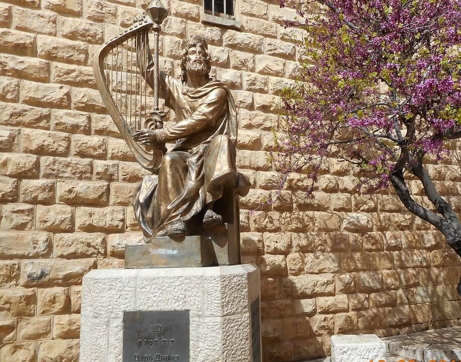 На фото изображена статуя царя Давида, который играет на арфе.