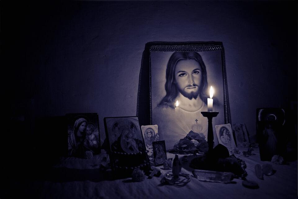 На фото изображены иконы, стоящие на столе и горящая свеча.