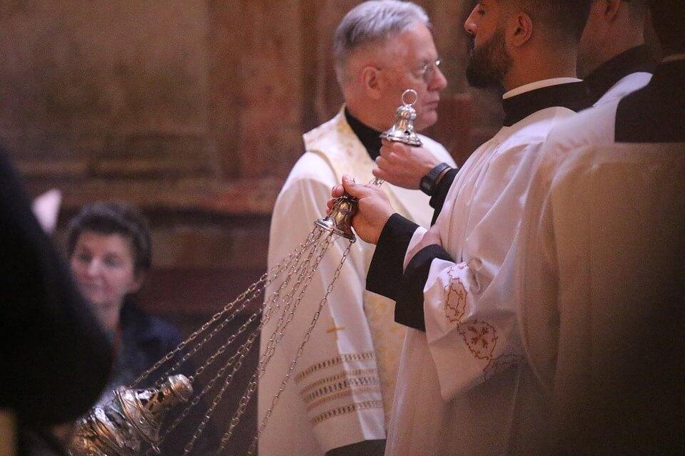 На фото изображен священник с кадильником.
