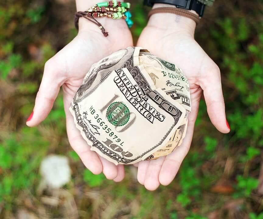 На фото изображены доллары в руках.