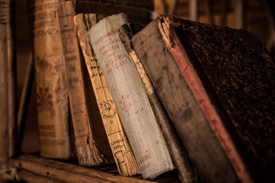 На фото изображены старые книги на полке.