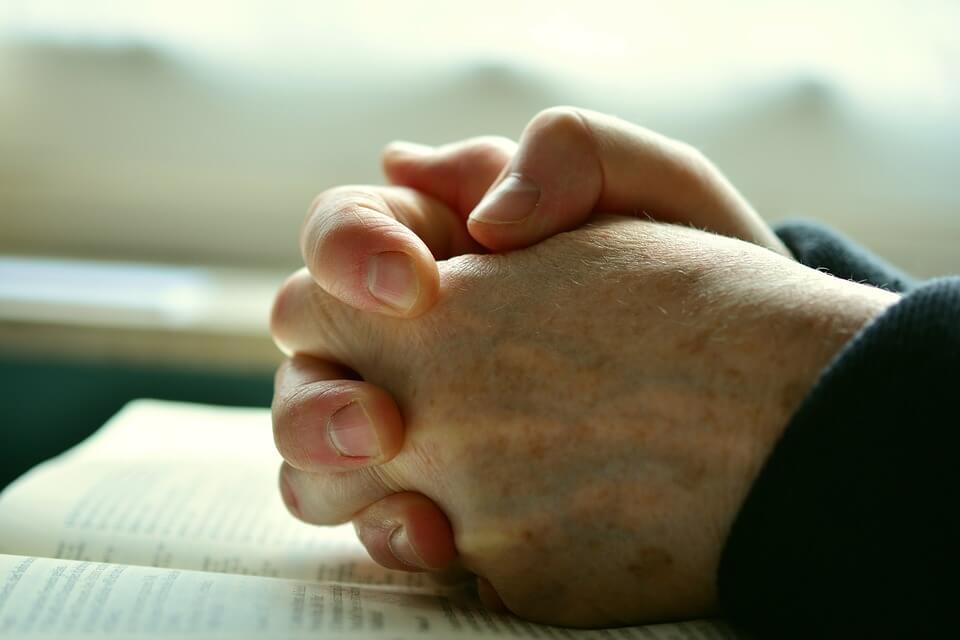 На фото изображены, сложенны в молитве, которые лежат на Библии.