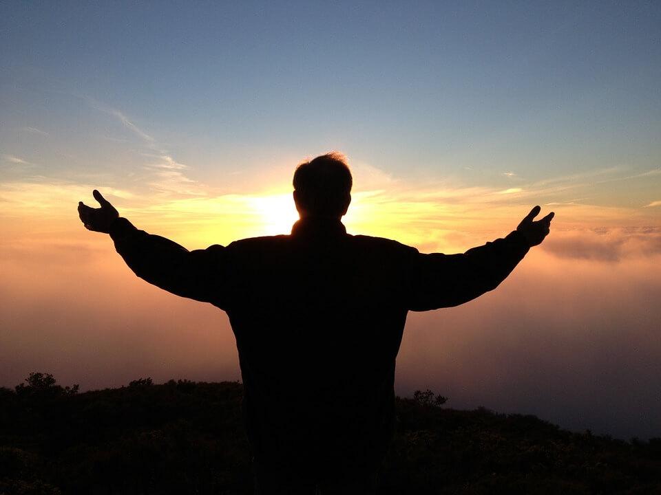 На фото изображен мужчина с распростертыми руками к небу.