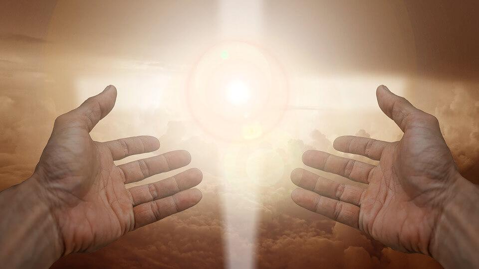 На фото изображены руки, возведенные в небо и свет в небесах.