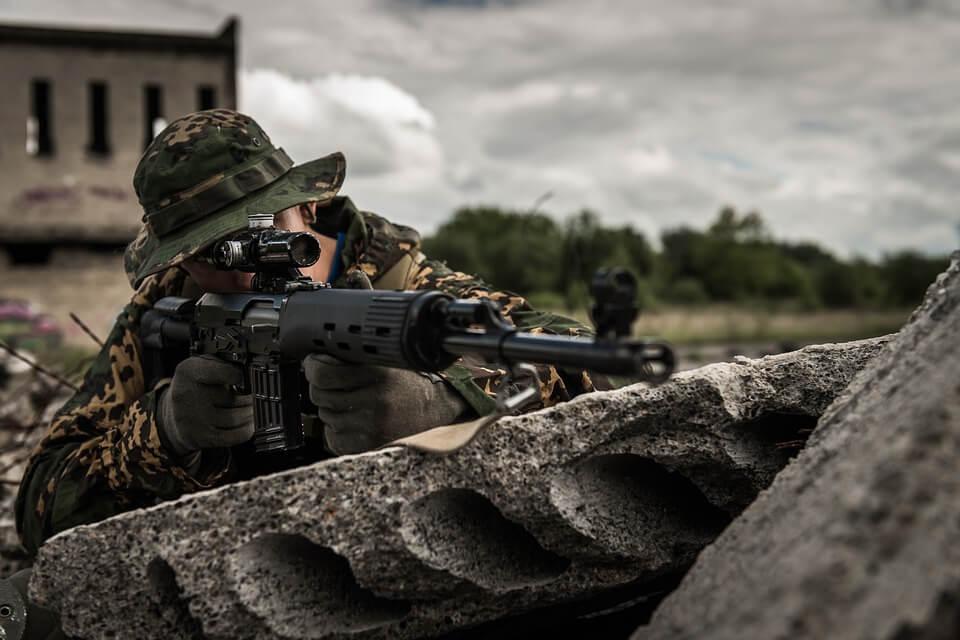 На фото изображен солдат с оружием.
