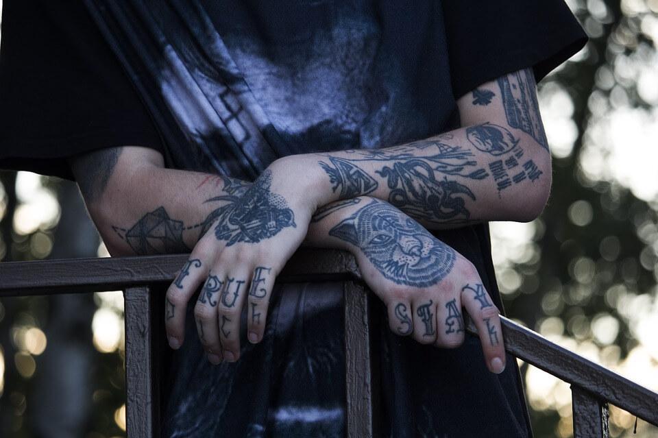 На фото изображены руки в татуировках.