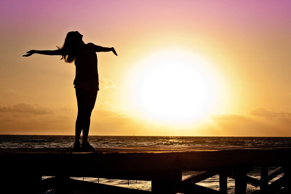 На фото изображена свободная женщина на фоне заката.