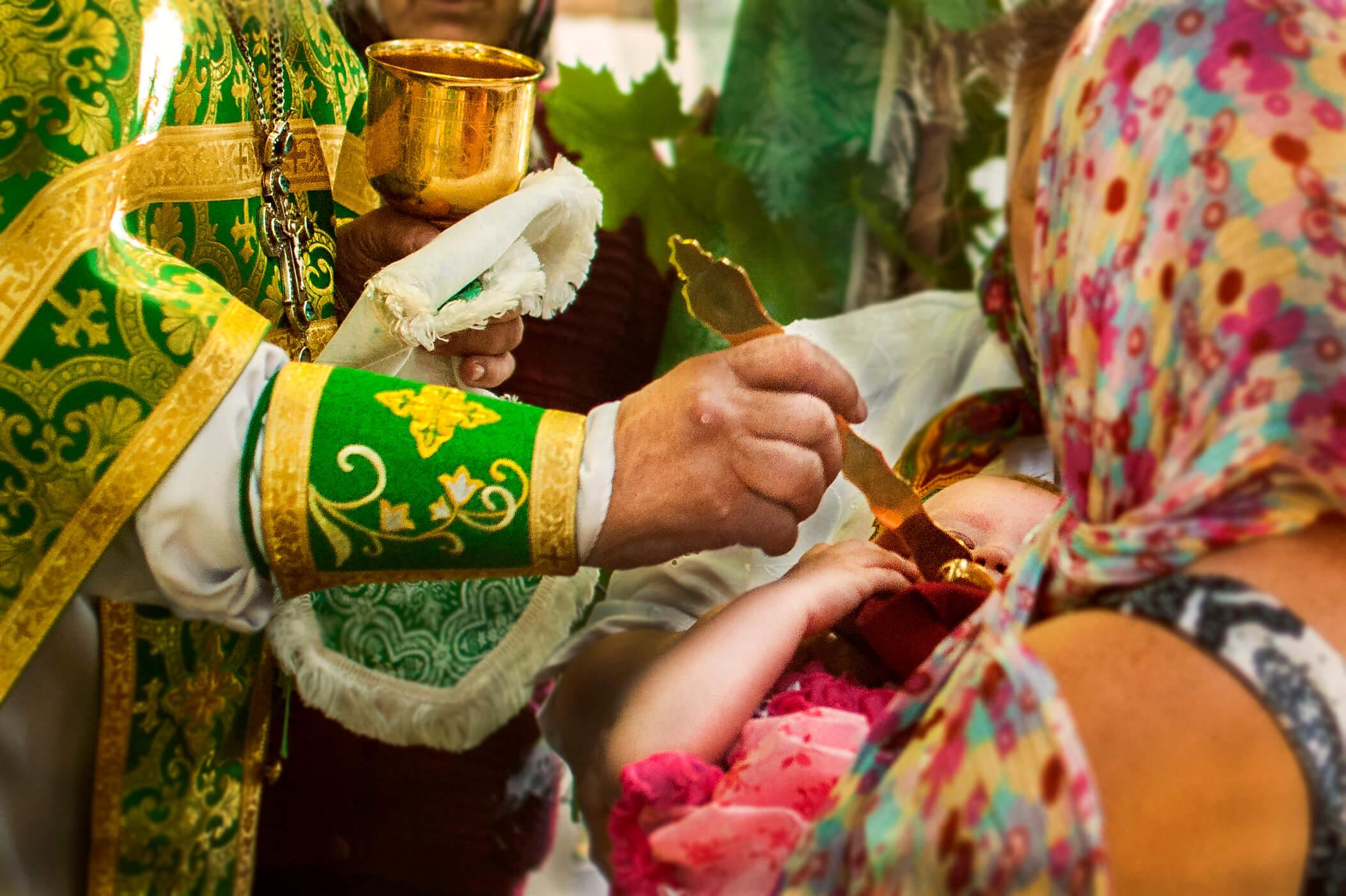 На фото изображена церемония причастия младенца.