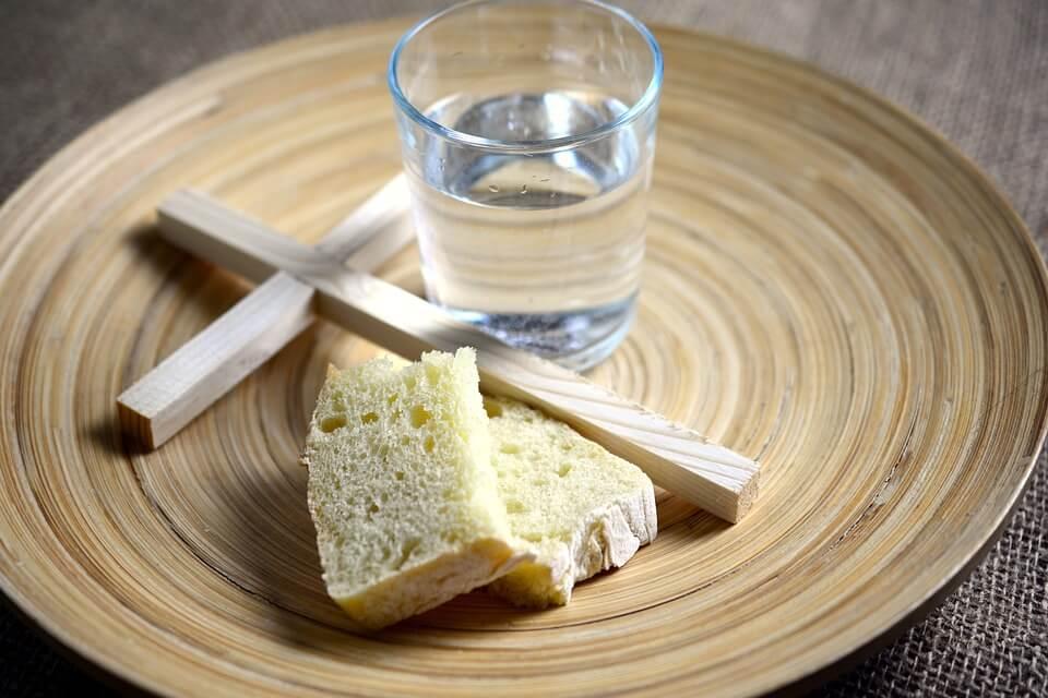 На фото изображен злеб, стакан воды и крест на тарелке.