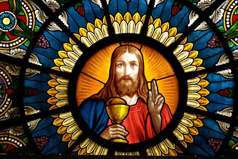 На фото изображено окно алтаря, на котором изображен Иисус с чашей.