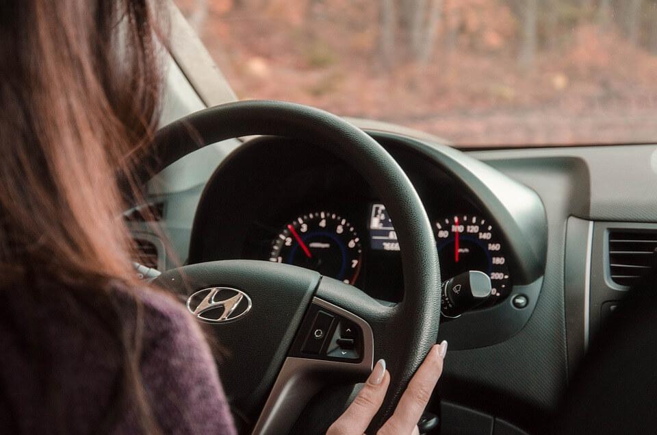 На фото изображена девушка за рулем автомобиля.