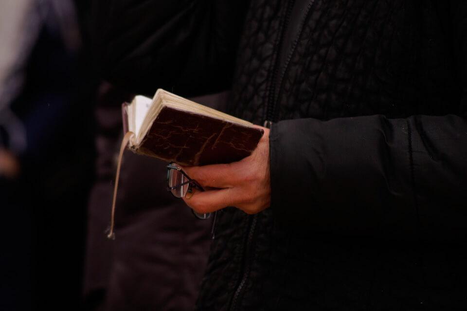 На фото изображено, как женщина держит в руках открытый молитвослов.
