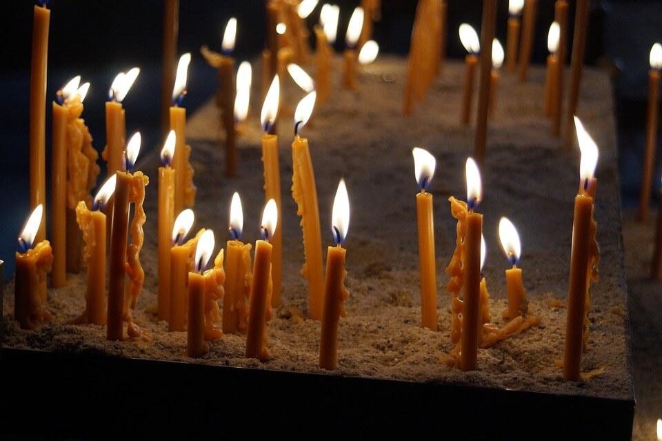 На фото изображены горящие свечи в песке.