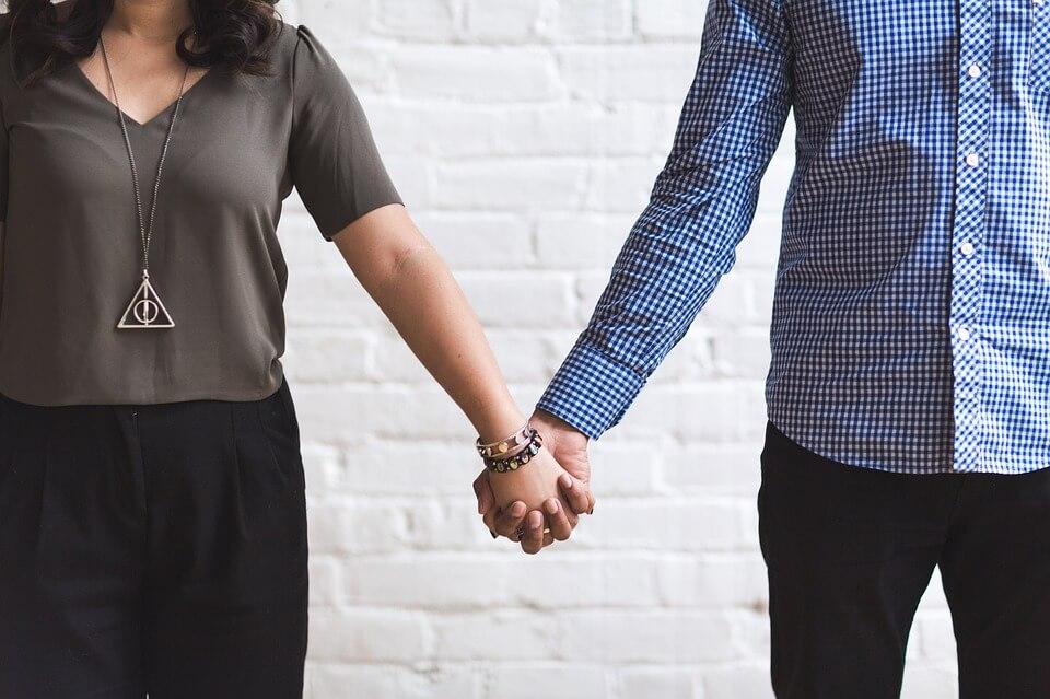 На фото изображена пара, которая держится за руки.