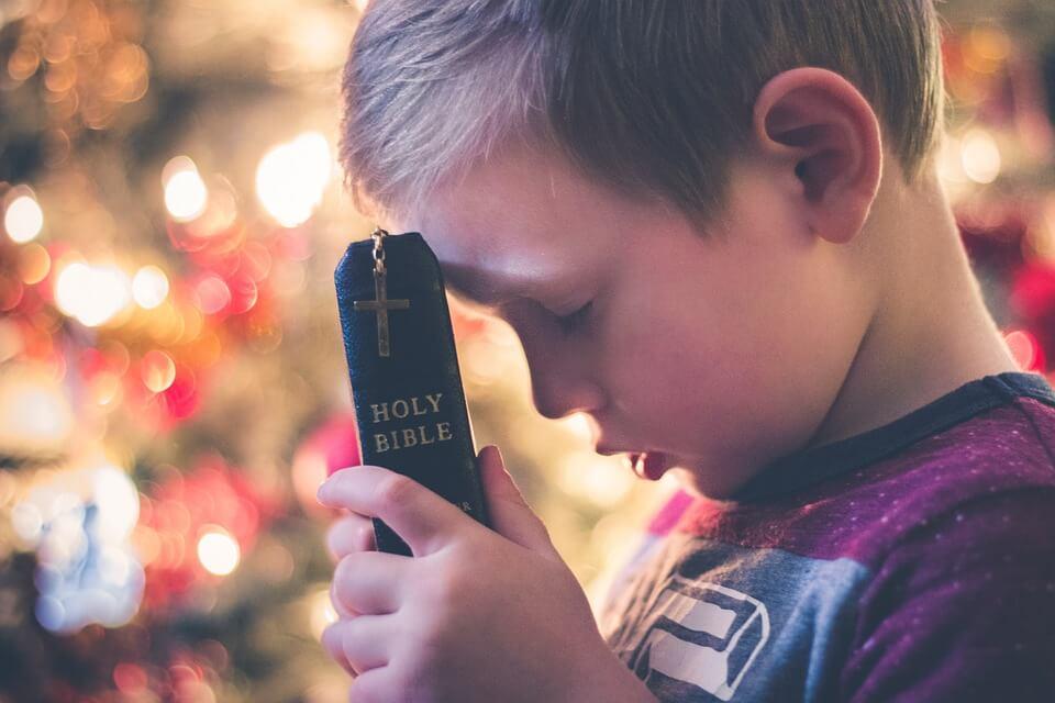 На фото изображен маленький мальчик с Библией.