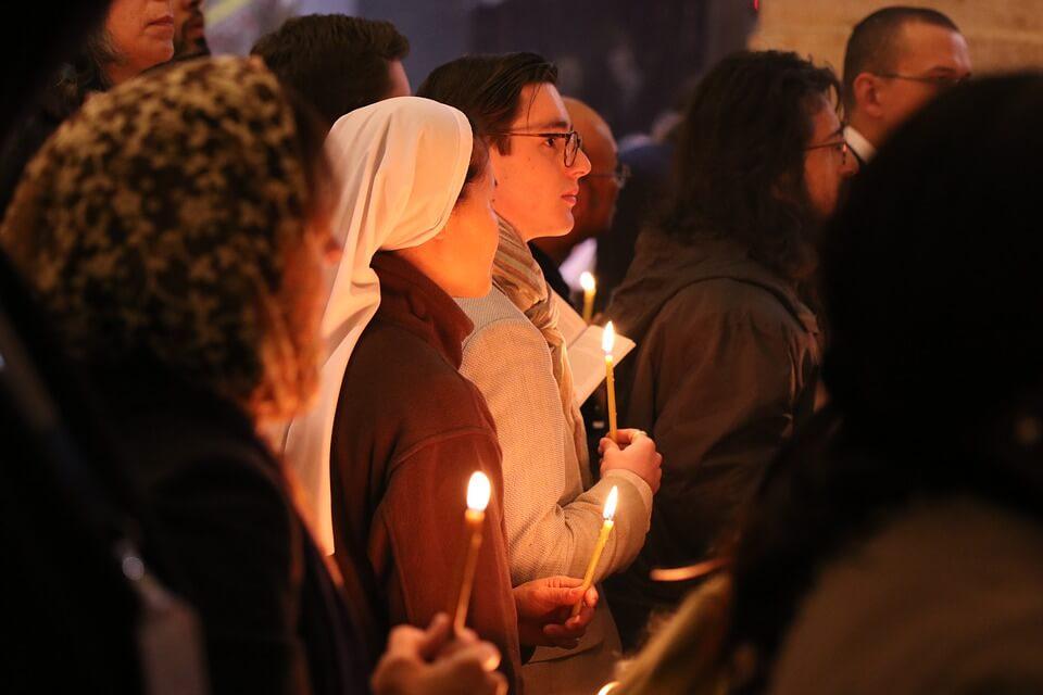 На фото изображены люди, стоящие на службе в церкви.