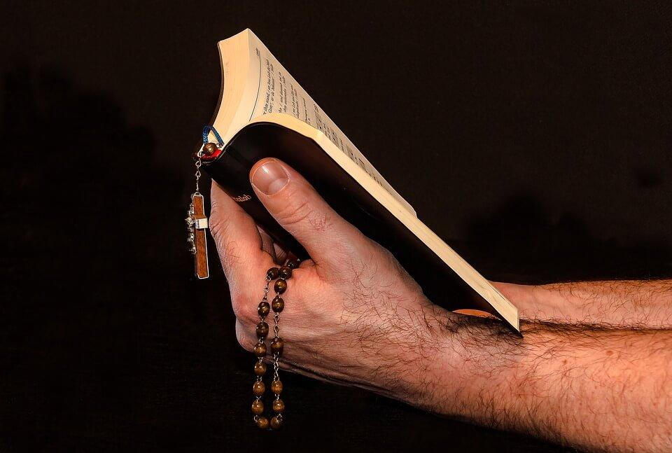 На фото изображено, как кто-то молится, читая текст из молитвенника.