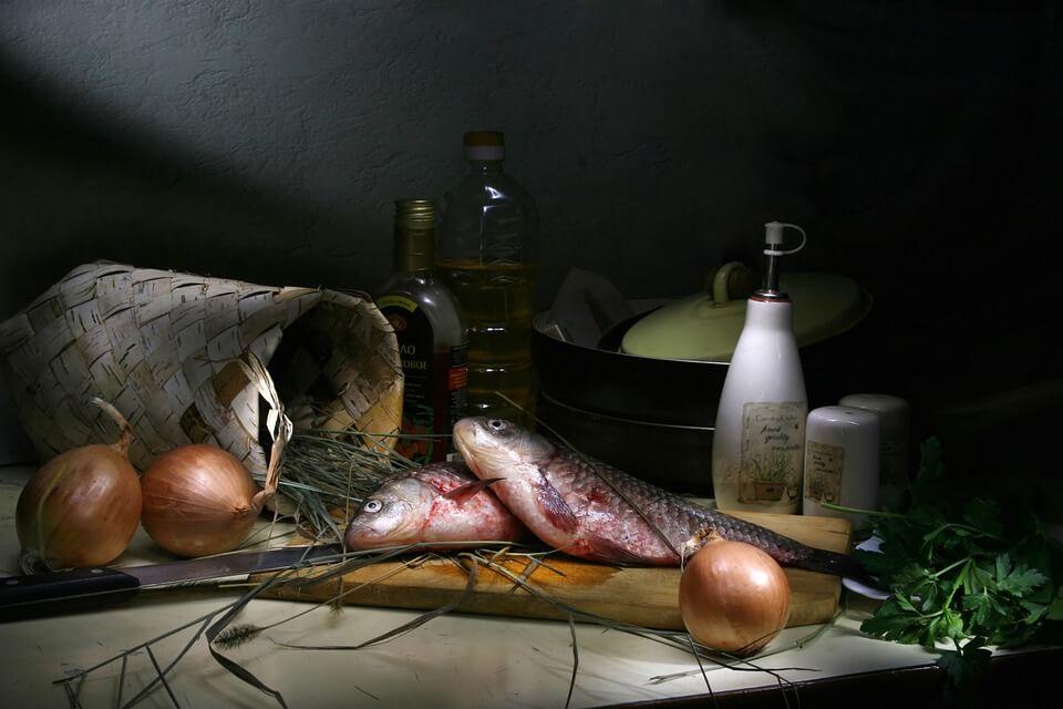 На фото изображена рыба на столе, специи, лук.