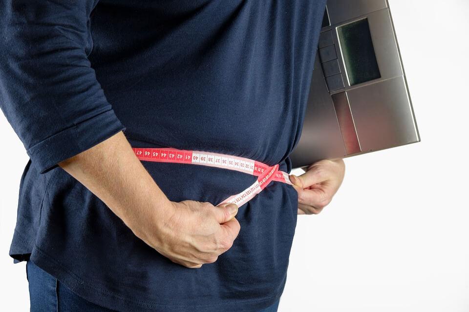 На фото изображено, как меряют талию и держат электронные весы.