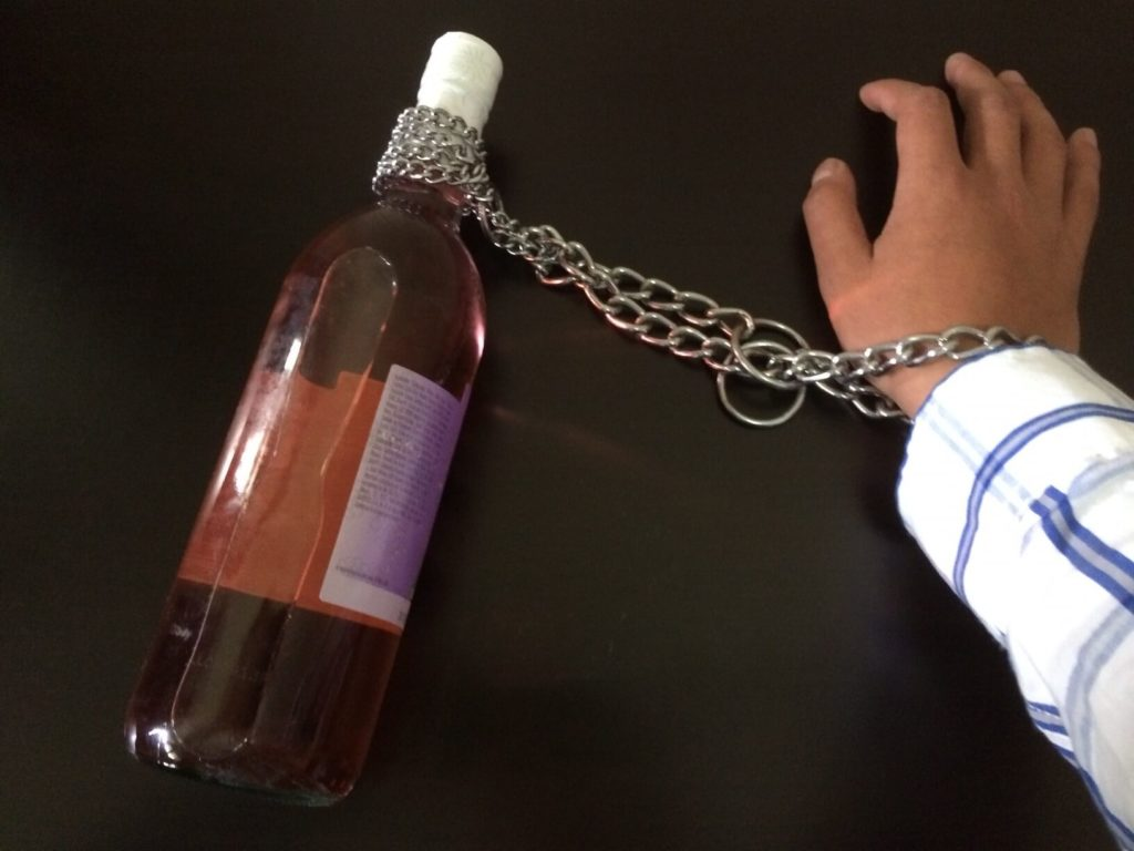 На фото изображена бутылка вина привязана к руке цепью.