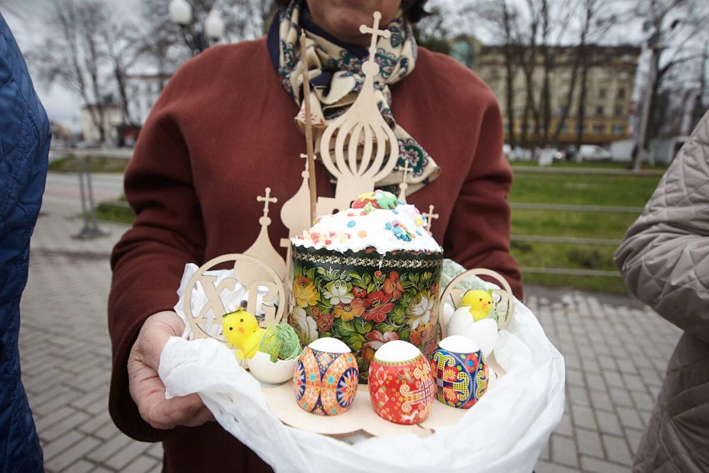 На фото изображен пасхальный кулич и крашенные яйца на блюде.