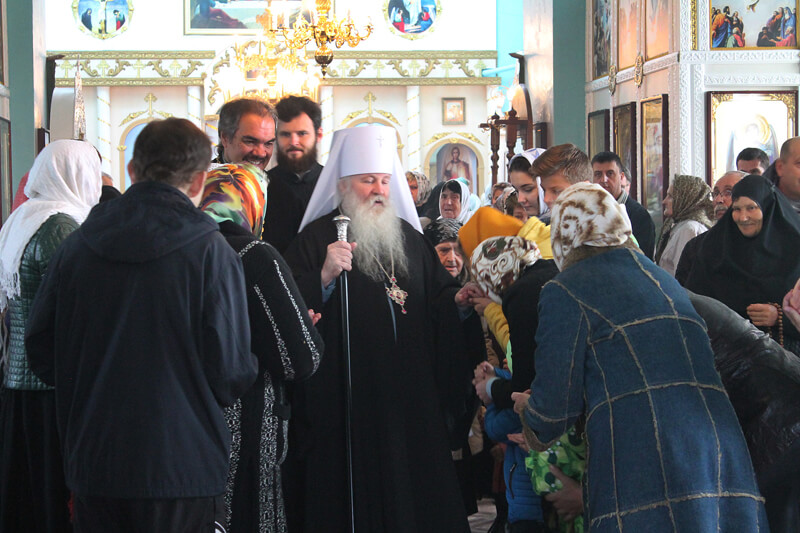 На фото изображен батюшка церкви среди прихожан.
