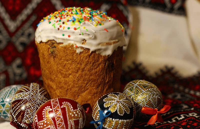 На фото изображены крашенные яйца и пасхальный кулич.
