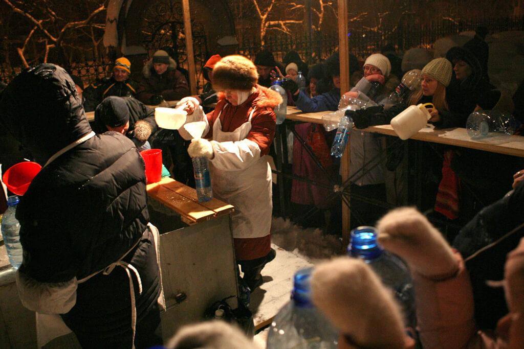 На фото изображено как люди набирают святую воду.