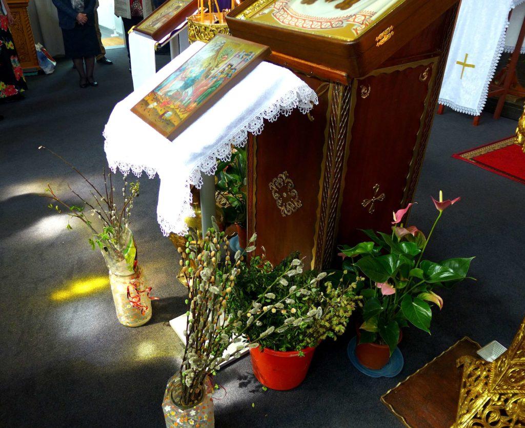 На фото изображены вербовые веточки в вазах в церкви.