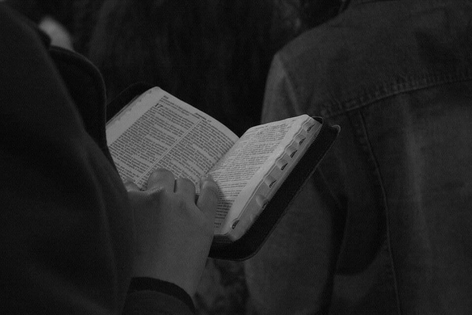На фото изображено, как человек читает Библию.