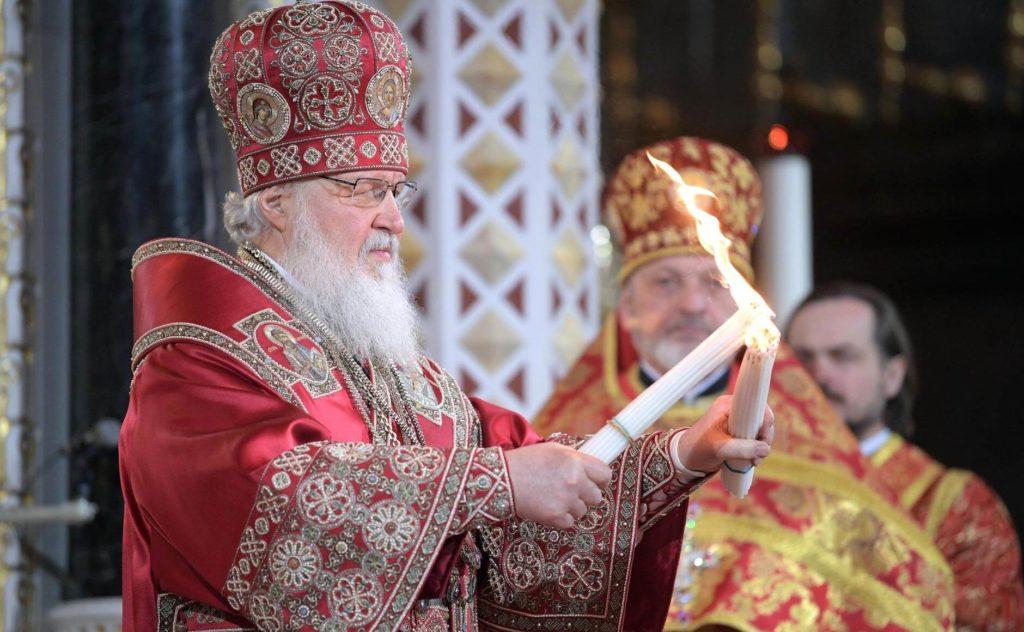 На фото изображено, как священник зажигает свечи благодатным огнем.