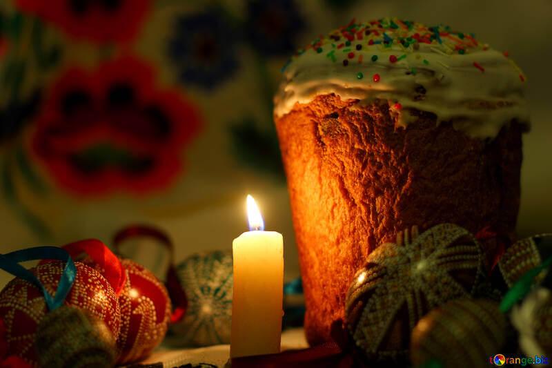 На фото изображен пасхальный кулич, крашанки и горящая свеча.