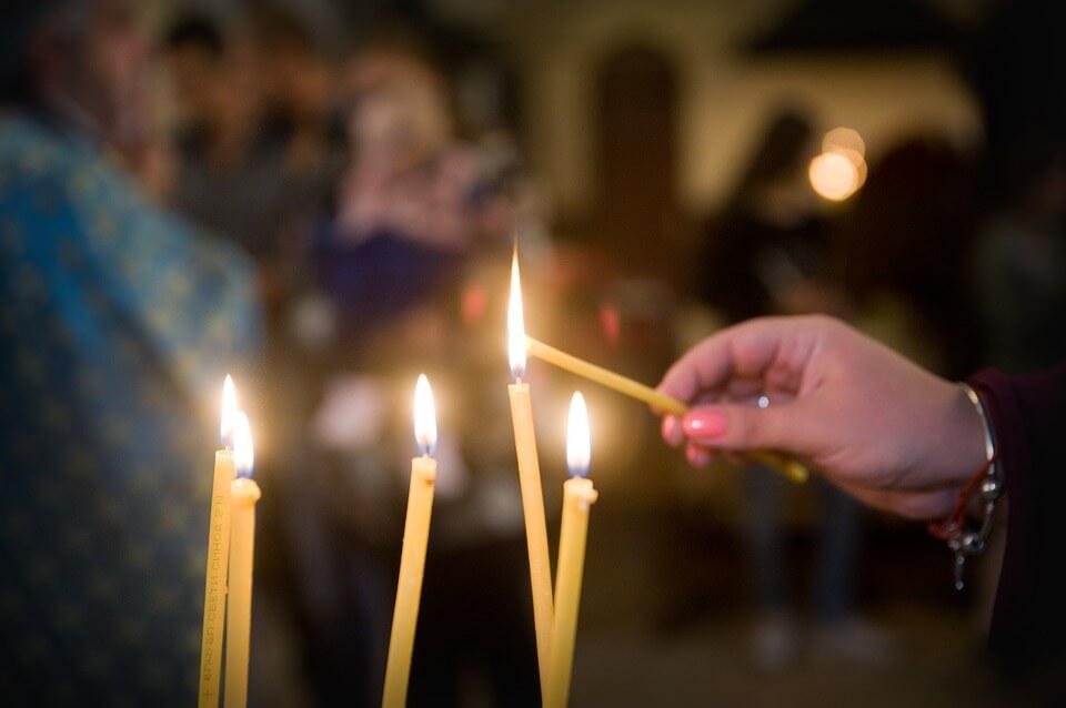 На фото изображено, как ставят свечу в церкви.
