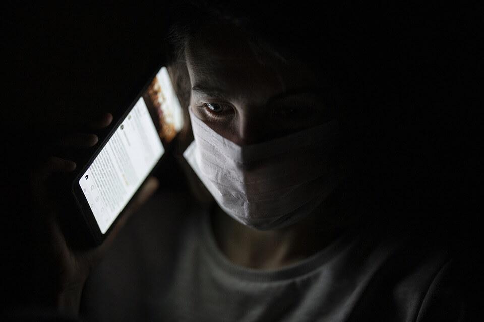 На фото изображен человек в медицинской маске, который звонит по телефону.