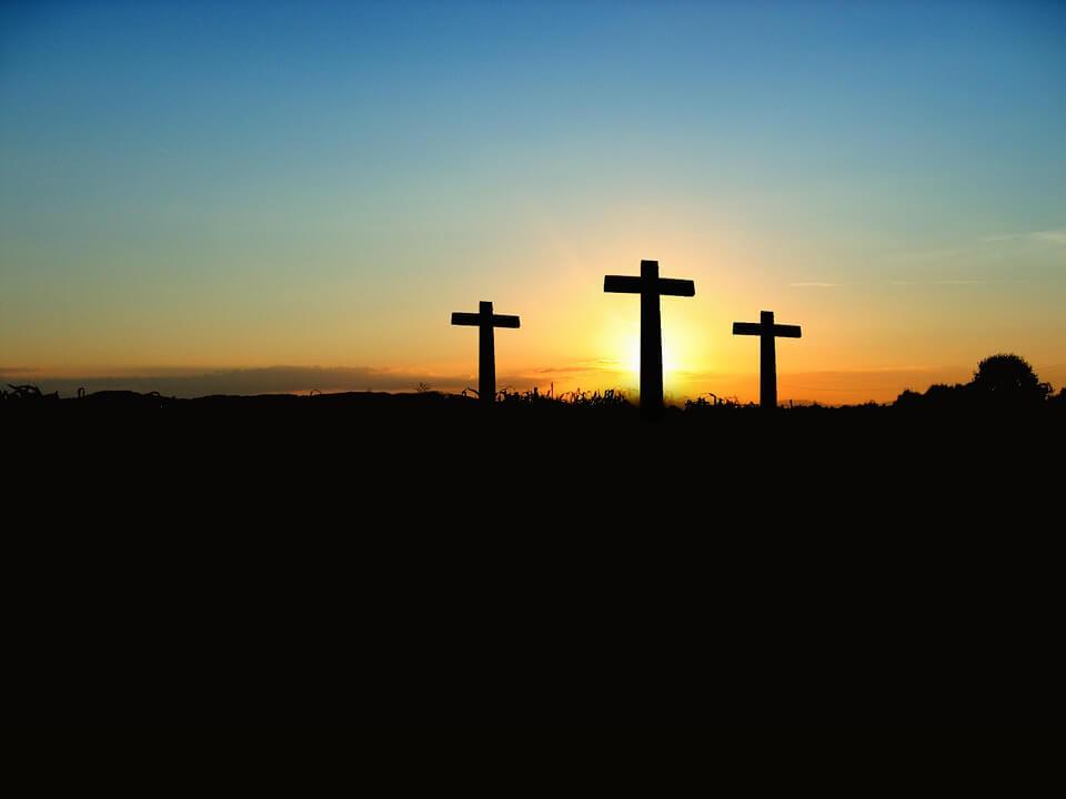 На фото изображены три креста на холме на фоне заката.