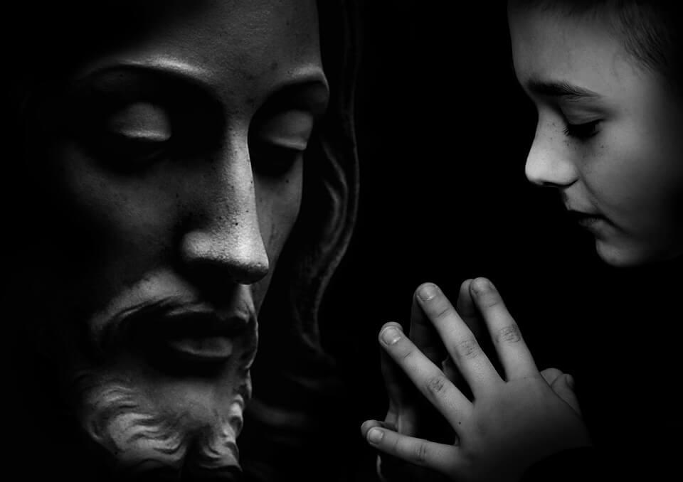 На фото изображен Иисус и девочка, которая молится.