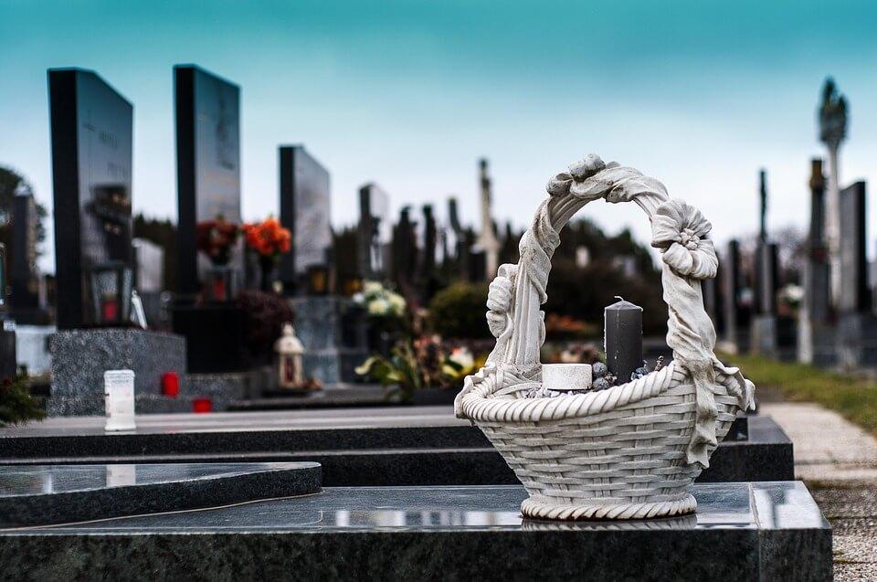 На фото изображена корзина со свечей на могиле.