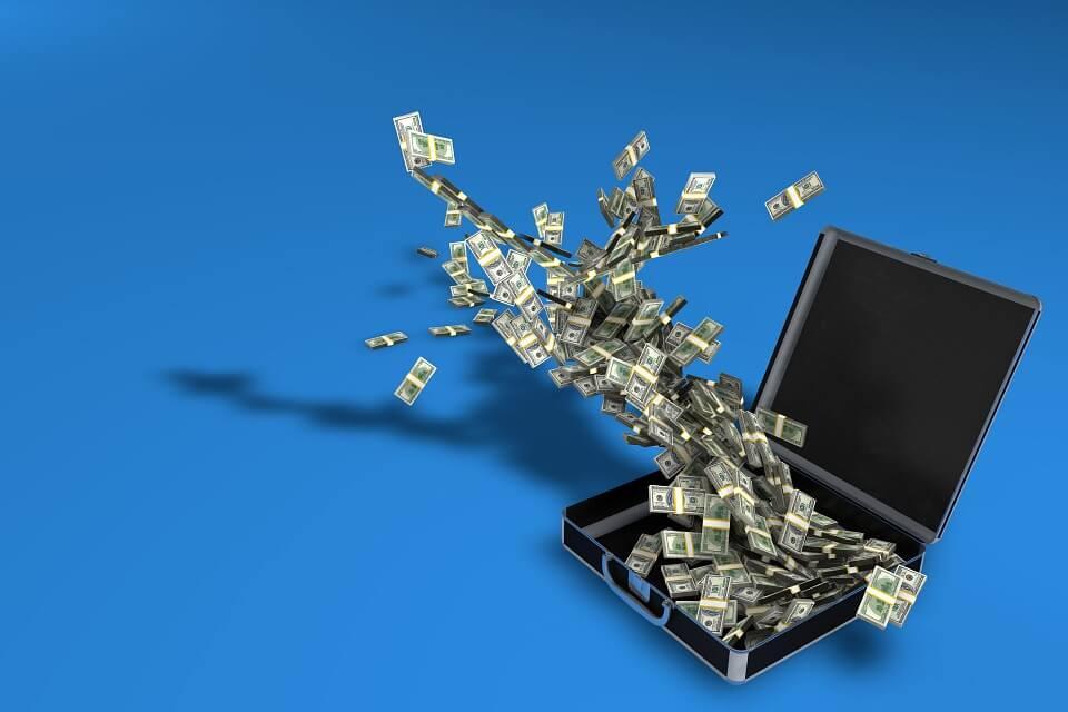 На фото изображен чемодан с деньгами.
