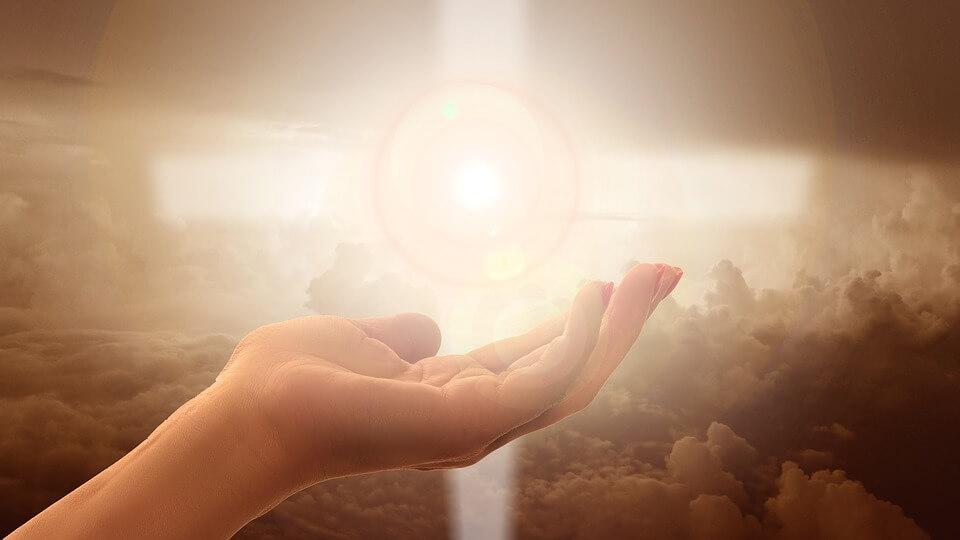 На фото изображен свет в небе и рука человека, которая тянется к нему.