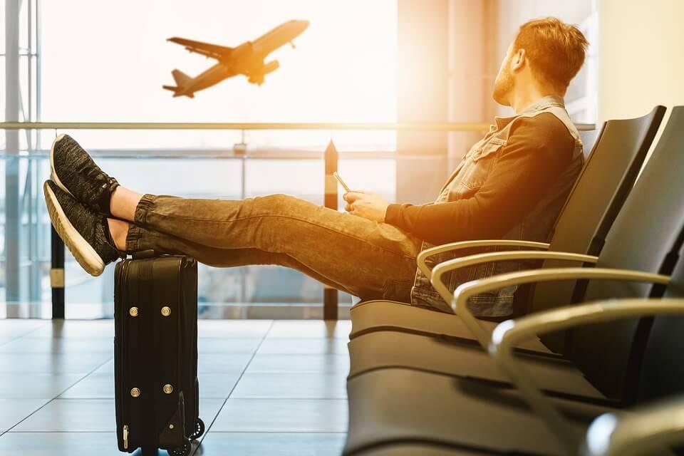 На фото изображен человек в аэропорту и взлетающий самолет.