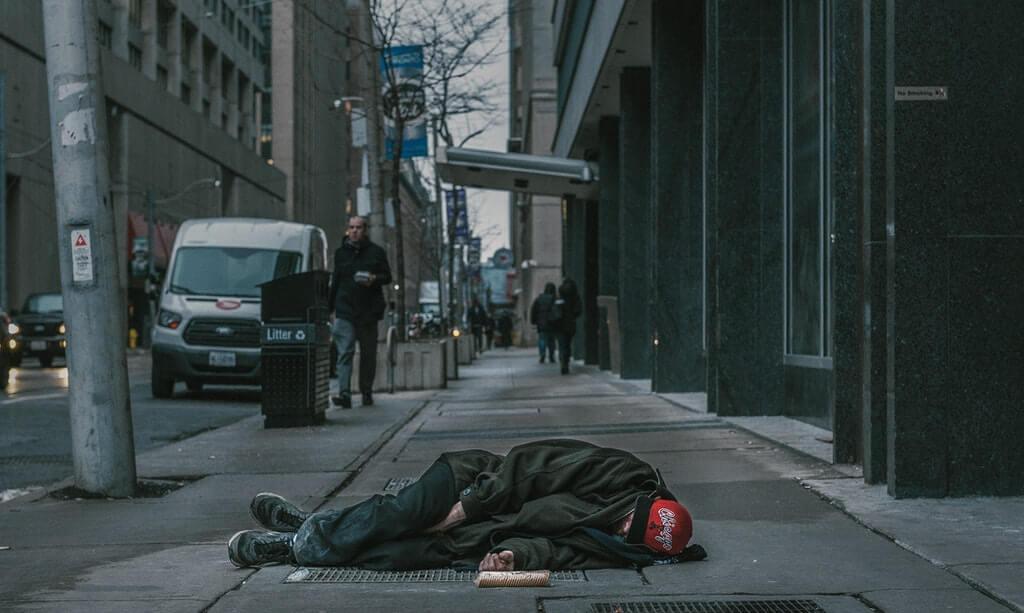 На фото бездомный человек лежит на дороге.
