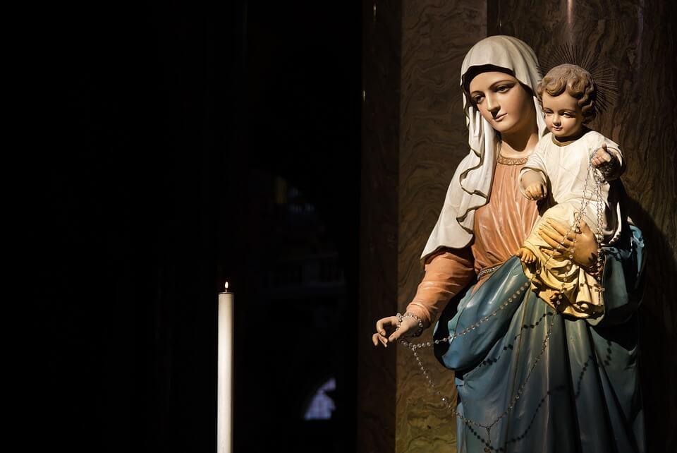На фото изображены дева Мария и Иисус возле свечи.