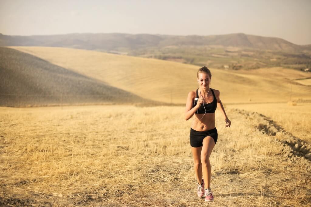 На фото изображена девушка, которая бежит по полю.