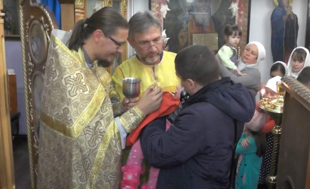 На фото причастие детей в храме.