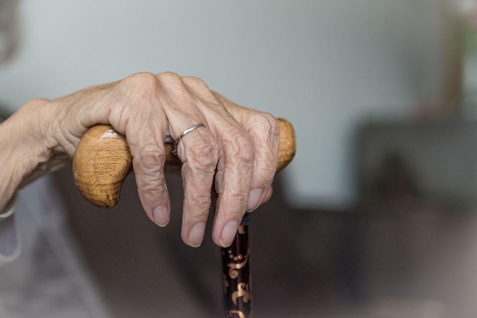 На фото изображена рука пожилого человека, который держится за тросточку.