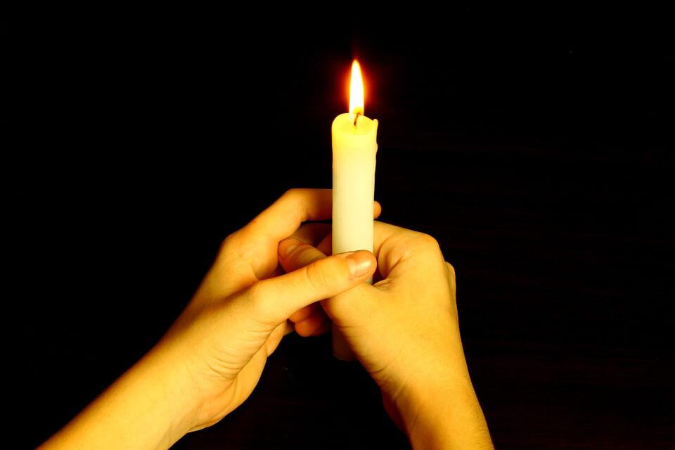 На фото изображена горящая свеча в руках.