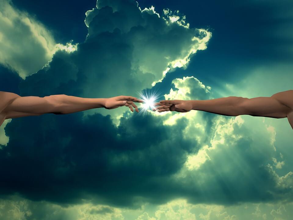 На фото изображены в небе две руки, которые тянутся друг к другу.