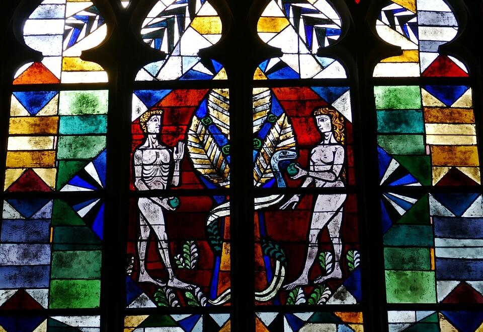 На фото изображен витраж на окне, где изображены Адам и Ева с запретным плодом.