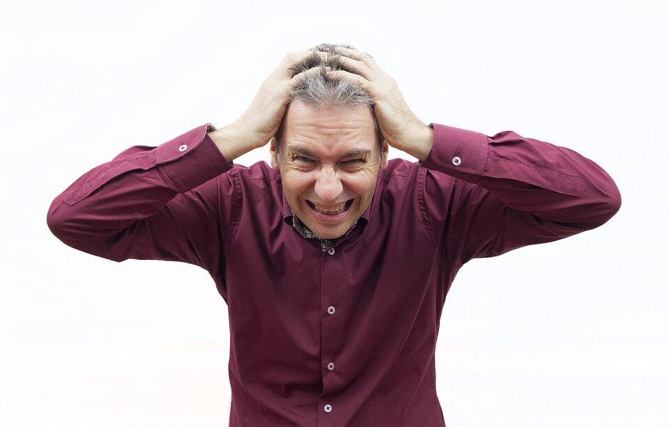 На фото изображен мужчина в стрессе, который держится руками за голову.